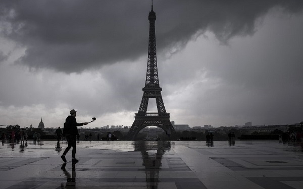 A man takes pictures as he enjoys the scenery of the Eiffel Tower from Trocadero after a rain shower in Paris on August 10, 2017. / AFP PHOTO / PHILIPPE LOPEZ