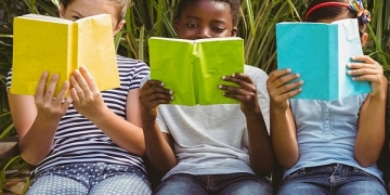 Children sitting in row and reading books at the park