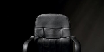 A detailed image of an empty, black, office chair