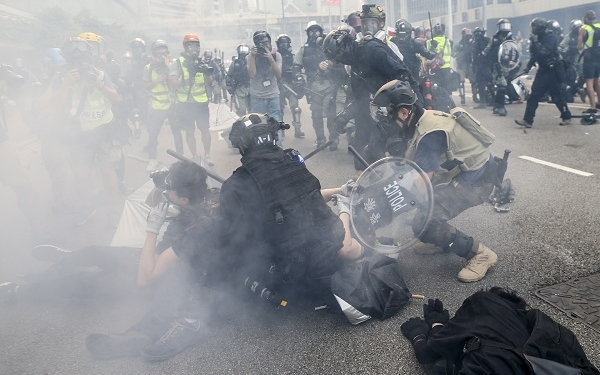 epa07879313 Policemen arrest anti-government protesters during a clash in the global anti-totalitarian march in Hong Kong, China, 29 September 2019. Hong Kong has entered its fourth month of mass protests, originally triggered by a now suspended extradition bill to mainland China, that have turned into a wider pro-democracy movement.  EPA-EFE/JEROME FAVRE