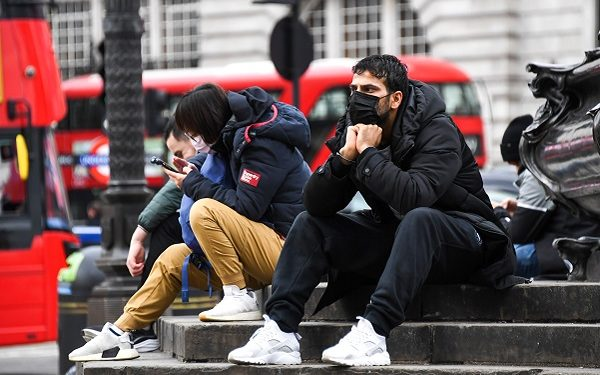 People wear face masks as they sit on the Shaftesbury Memorial Fountain in Piccadilly Circus, in London, Friday, March 13, 2020. For most people, the new coronavirus causes only mild or moderate symptoms, such as fever and cough. For some, especially older adults and people with existing health problems, it can cause more severe illness, including pneumonia.(AP Photo/Alberto Pezzali)