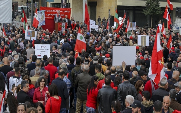 epa07235413 Supporters of the Lebanese communist party along with activists from the civil society wave the party flags with Lebanese flags and placards during a protest in Beirut, Lebanon, 16 December 2018. Hundreds of protesters from the National Union of Trade Unions and Users in Lebanon, led by the Lebanese Communist Party and the Lebanese Democratic Youth Union, protested in front of the headquarters of the Banque du Liban and marched towards down town Beirut, rejecting unfair taxes on gasoline and value added (TVA) and all indirect taxes, calling on the government to protect citizens right to work and right to have access to medical care.  EPA-EFE/NABIL MOUNZER