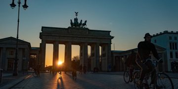epa08320315 Cyclists ride through the Brandenburg Gate at dawn in Berlin, Germany, 24 March 2020 (issued 25 March 2020).  EPA-EFE/ALEXANDER BECHER