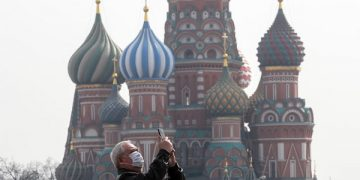 epa08330019 An elderly man wearing protective mask takes pictures in front of the cathedral of Vasily the Blessed on the Red Square in Moscow, Russia, 29 March 2020. Russian authorities recommended for all Russians do not leave their homes for nine days in order to stop the spread of the coronavirus Covid-19 disease. The next week was declared not working for evrebody, all restaurants, bars, shopping centers, cinemas and city parks were closed. According to the Russian Quarantine Service of Rospotrebnadzor (Russian Federal Service for Surveillance on Consumer Rights Protection and Human Wellbeing), eight people died and 1534 cases of the Covid-19 disease have been confirmed in Russia.  EPA-EFE/SERGEI ILNITSKY
